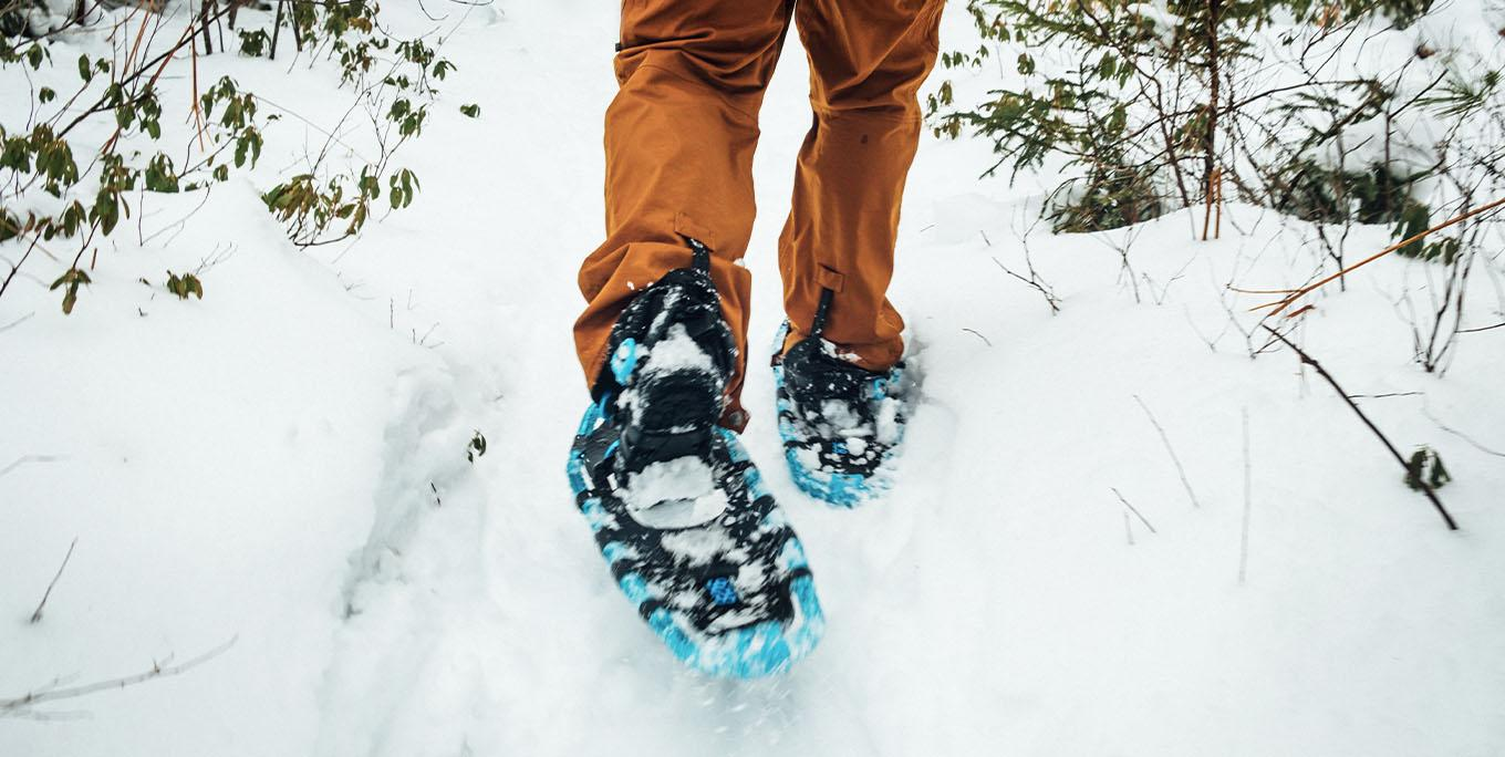 A man in orange snowpants and blue snowshoes walking through deep snow.