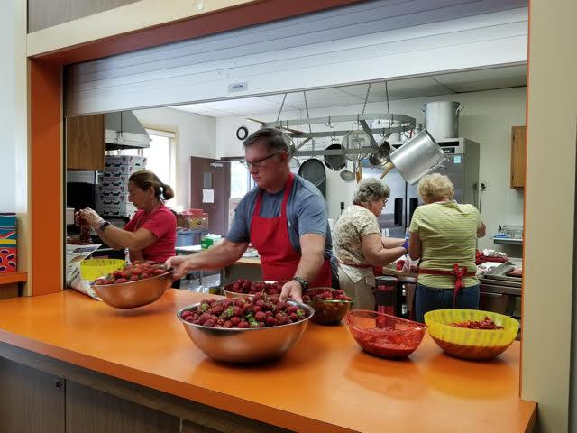 Kathy and Ken Hubacher preparing strawberries for St. Luke's Strawberry Social