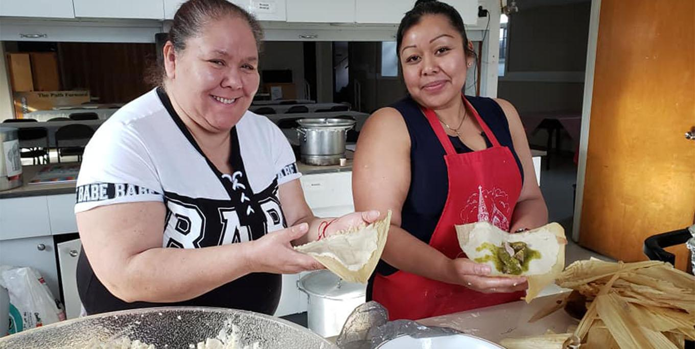 Gloria Ramos and Blanca Rodríguez making tamales in the kitchen of St. Michael's Church.