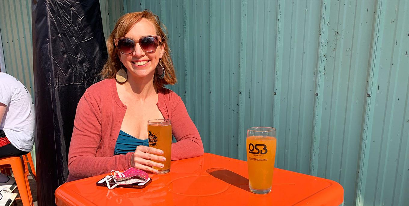 Sarah Keller sitting on the patio of OSB Ciderworks with two ciders on the table in front of her. Photo by Jon Kanelstein.