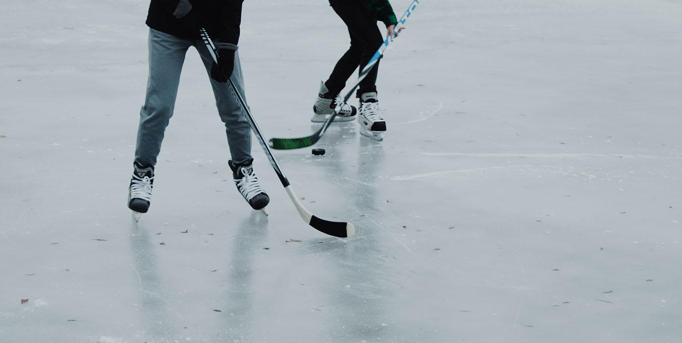 Two people playing ice hockey on an outdoor rink.