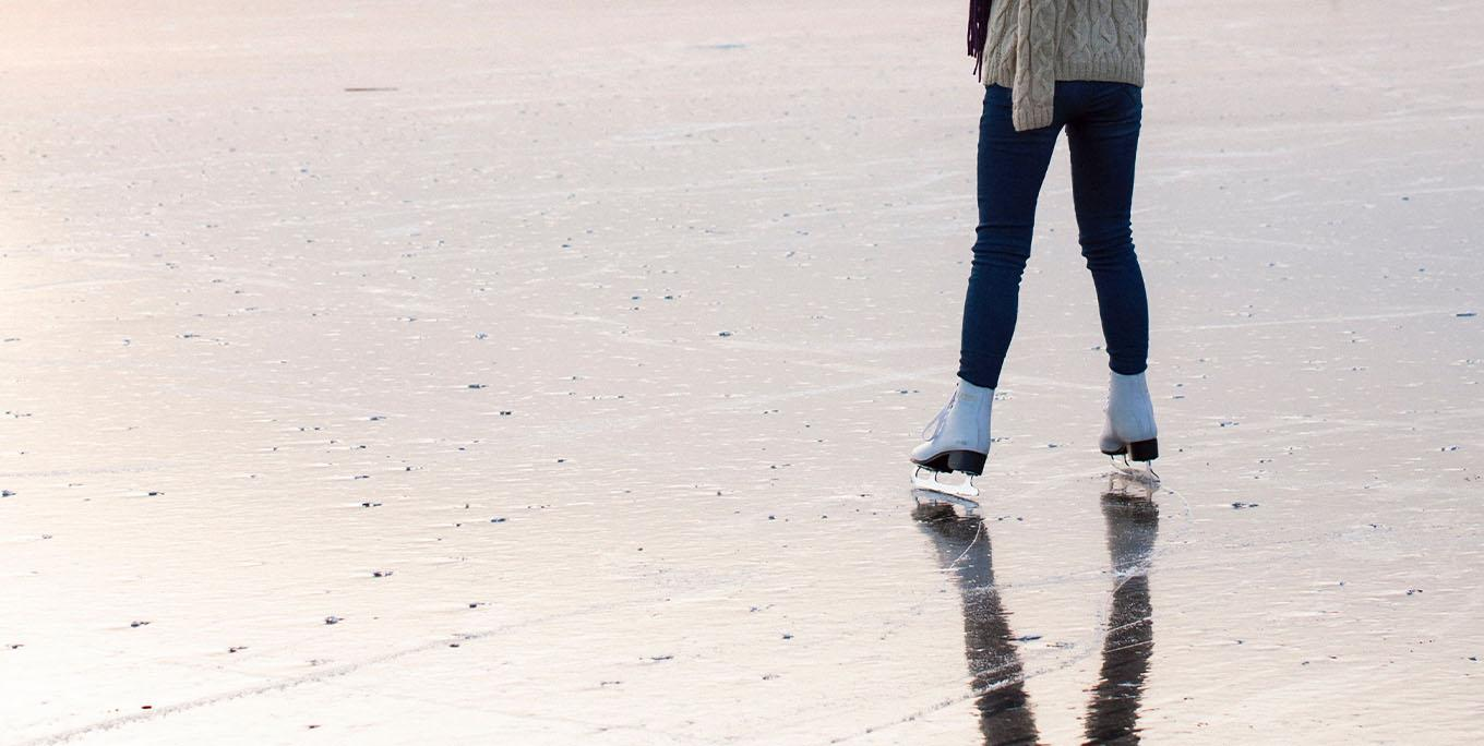 The bottom half of a woman ice skating outdoors.