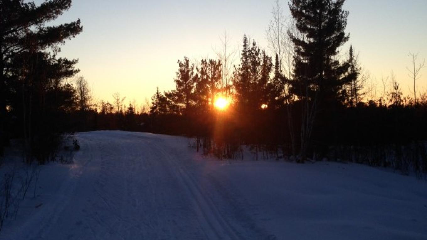 The sun dips toward the horizon. – Rainy Lake Nordic Ski Club