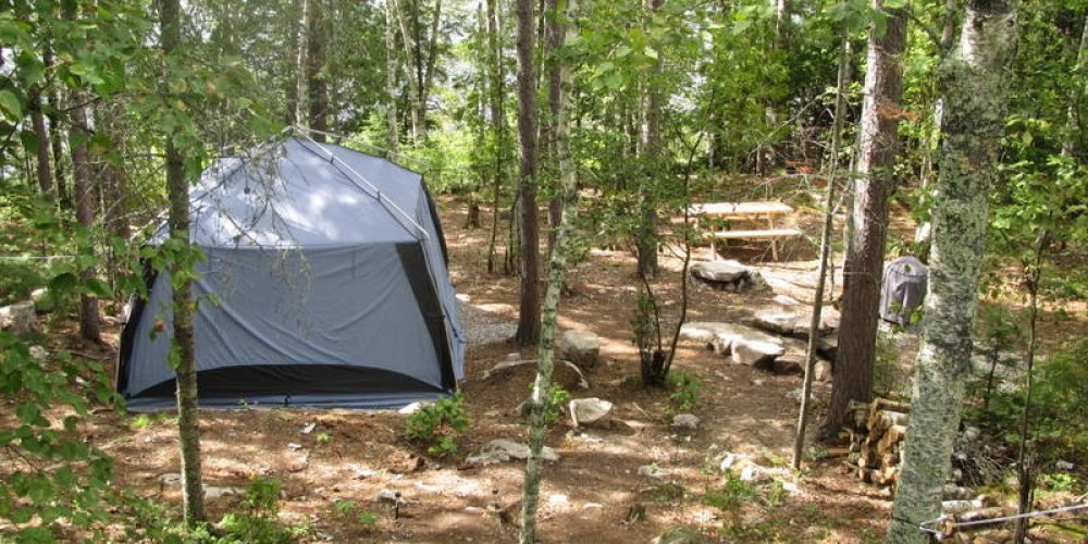 Looking down from the sleep tent at the cook tent , picnic table, and fire pit. – MaryAnn Pinckney