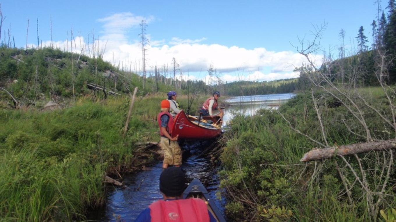 Campers navigate a tight stretch between lakes in the BWCA Wilderness – YMCA Camp Menogyn