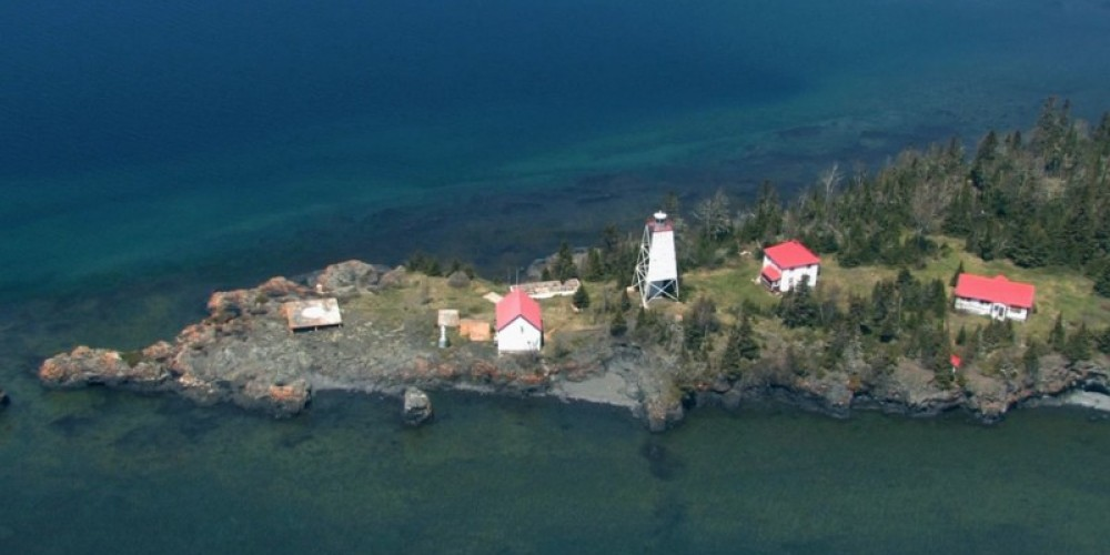 Aerial shot of the lighthouse site from a float plane. From L to R, you can see the Helipad, maintenance building, light tower, tourist accommodations, and administrative bunkhouse. The boathouse is not seen in this picture. – Photo by: P. Morralee