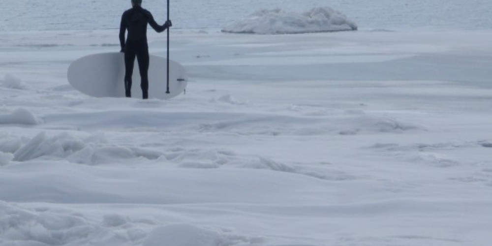 Co-owner/Founder Jake Boyce on Lake Superior Ice with stand-up paddleboard – Laura Francis