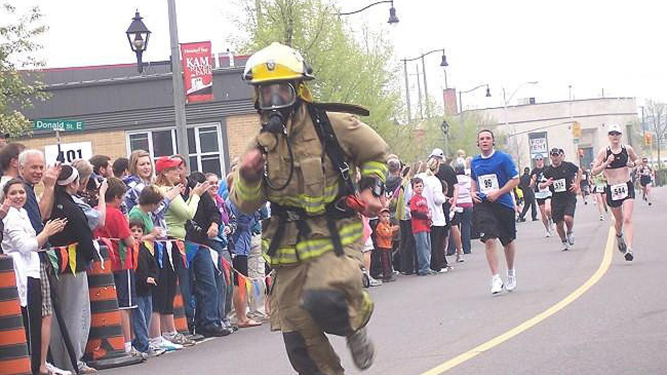Fire fighter in full gear cheered on my crowd of spectators lining the street. – Jim Cameron - 10-Mile Road Race