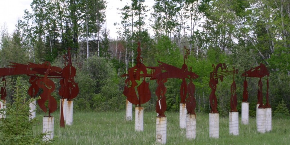 Basshenbge is a quirky roadside artwork featuring bass violin silhouettes cut from sheet steel and mounted on concrete pillars in the rough outline of Stonehenge. North side of highway just east of Birchdale. – international falls, rainy lake and ranier cvb