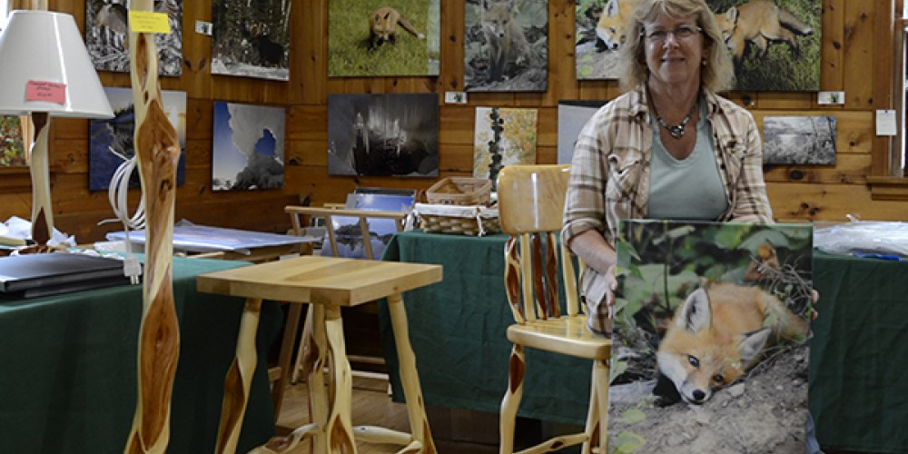 Sandra Updyke showing her photographs as she sits beside her husband Bruce's Diamond Willow furniture