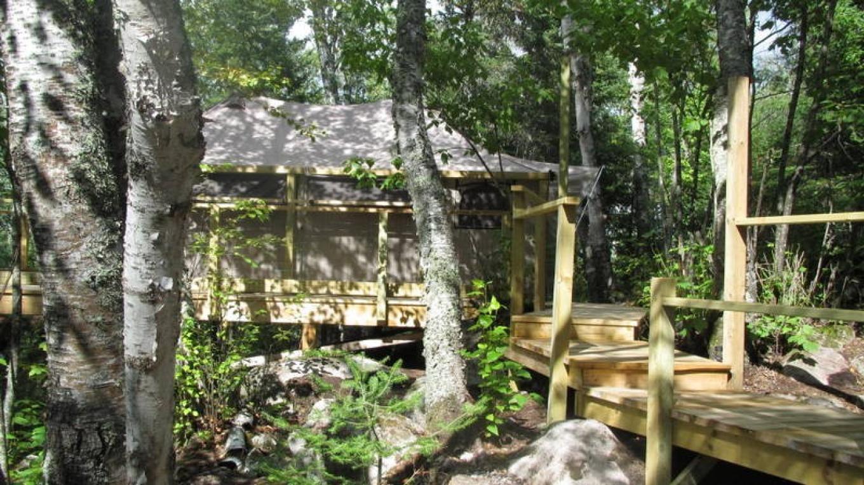 View of the sleep tent via the boardwalk from the sauna. – MaryAnn Pinckney