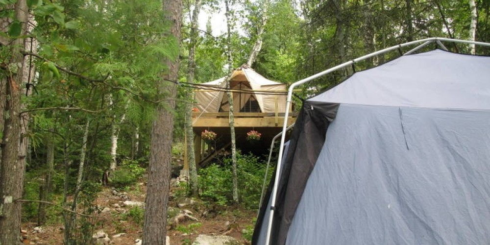 Looking up at the elevated sleep tent from the cook tent. – MaryAnn Pinckney