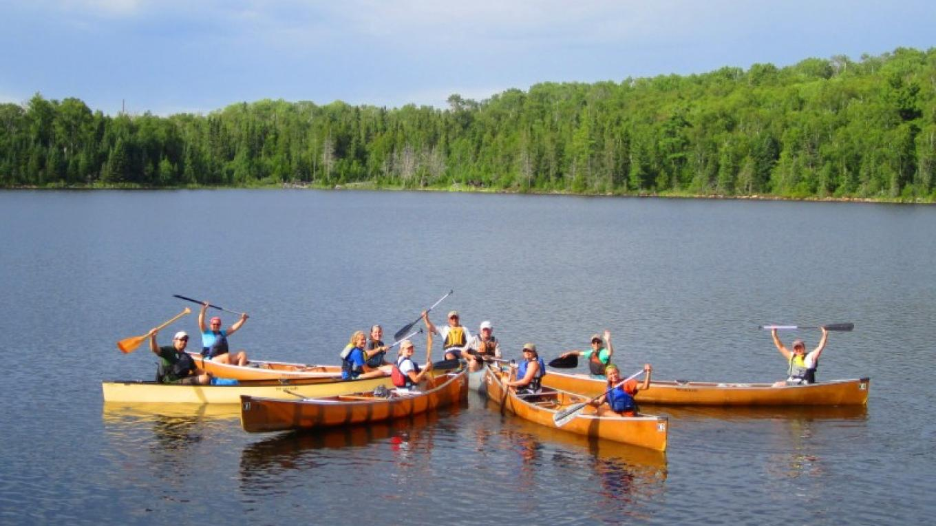 A family group enjoys paddling on Frear Lake in the Superior National Forest – H. Walz