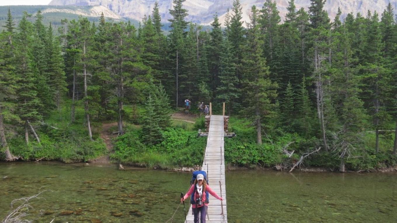 Crossing suspension bridge over the Belly River. – Courtesy Glacier Guides