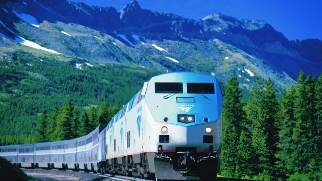 Amtrak Empire Builder trains along the edge of Glacier National Park. – Courtesy of Amtrak