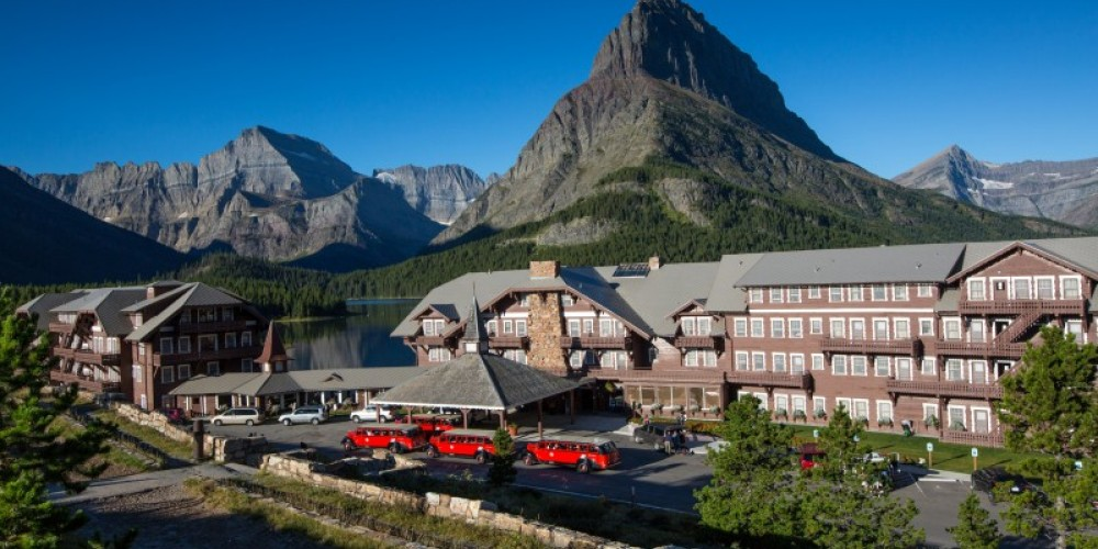 Many Glacier Hotel Front Exterior with famous Red Buses lined up. – Glacier National Park Lodges