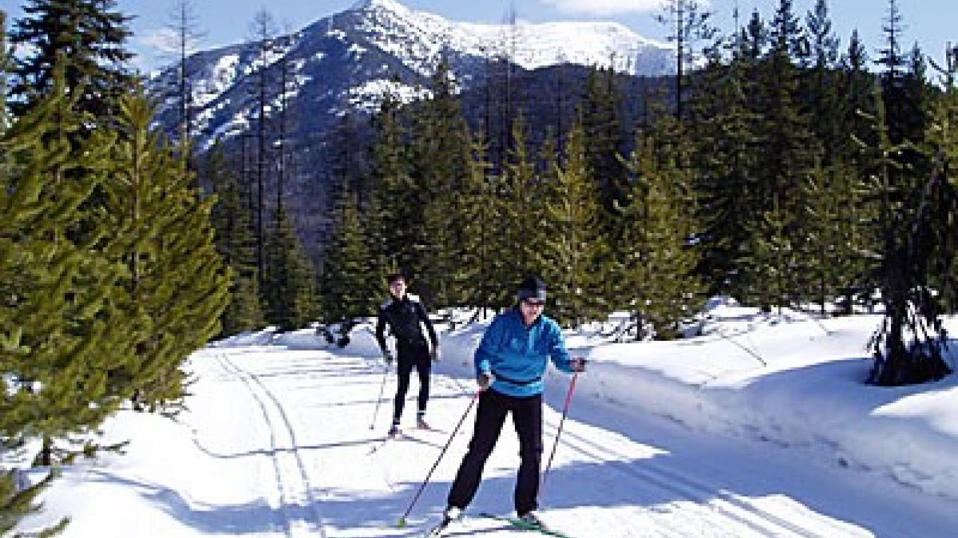 Skiing the Starlight Trail at Izaak Walton Inn. Glacier National Park's Running Rabbit Mountain forms the backdrop. – Ralph Thornton, Ear Mountain Photography, www.earmountain.com
