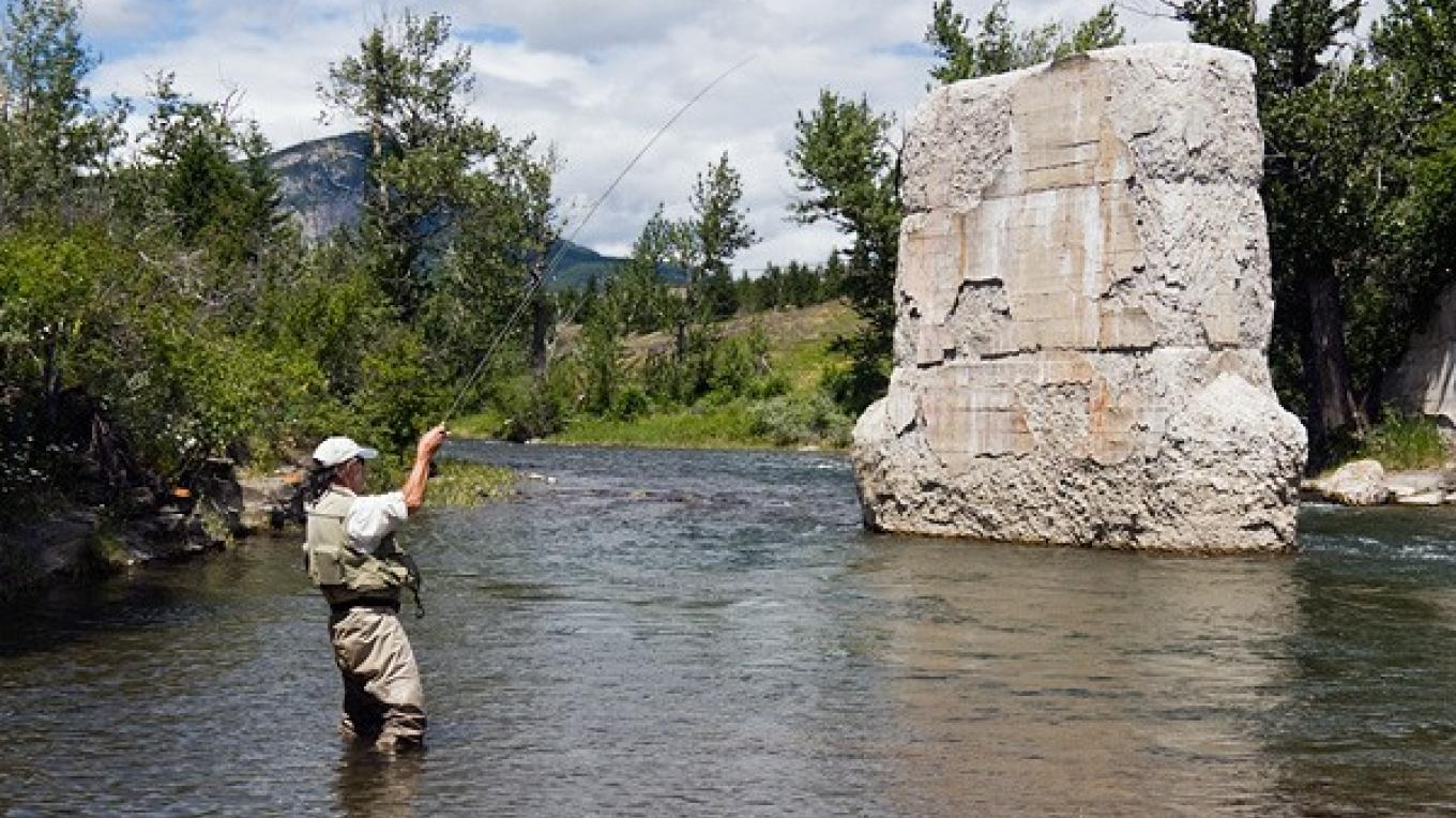 A fly fisher on the Crowsnest River, a short distance downstream of Turtle Mountain and the Frank Slide – Vic Bergman