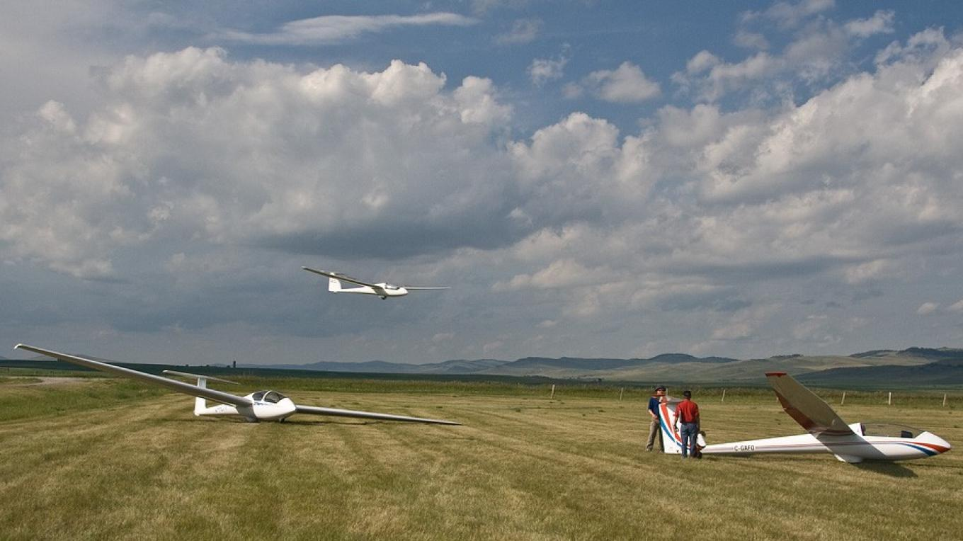 Soar plane descends as fliers prepare another to launch at Cowley glider camp. – David Thomas