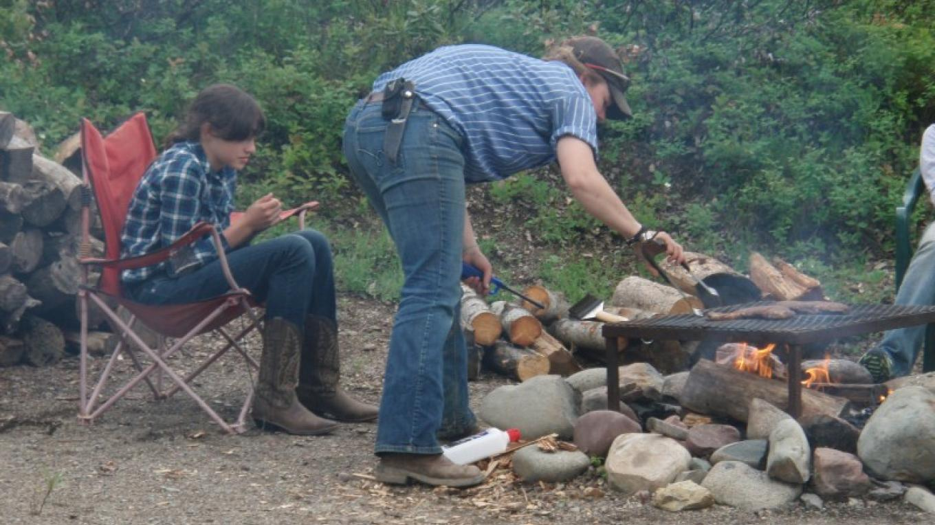 Cooking steaks over an open flame on the Cowboy Cookout ride out of the West Glacier Corral.