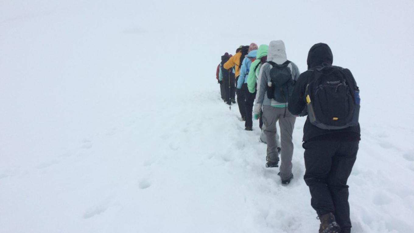 Course participants hiking through the snow in search of tracks and geology.