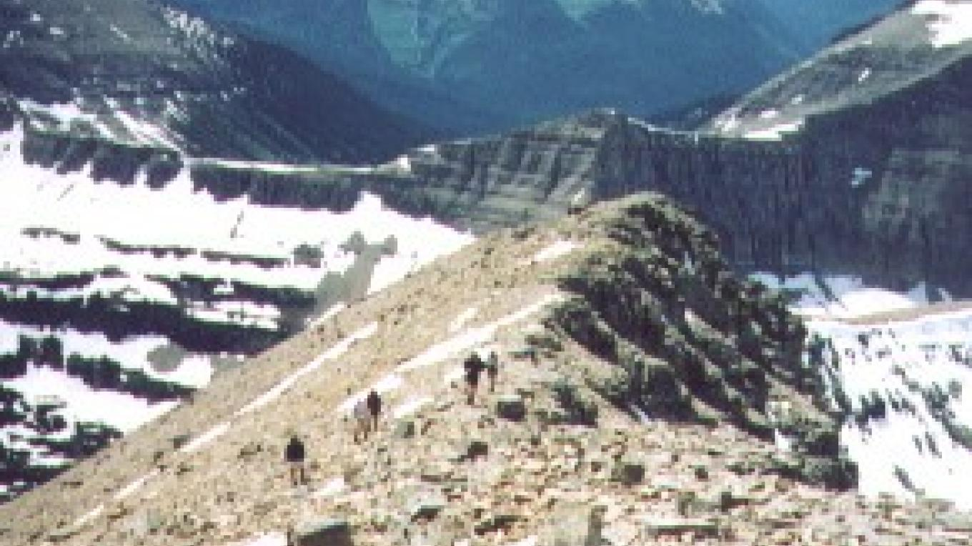 Hikers follow the ridgeline to Triple Divide Peak (foreground) – Tom Kotyinski, courtesy Great Falls Tribune
