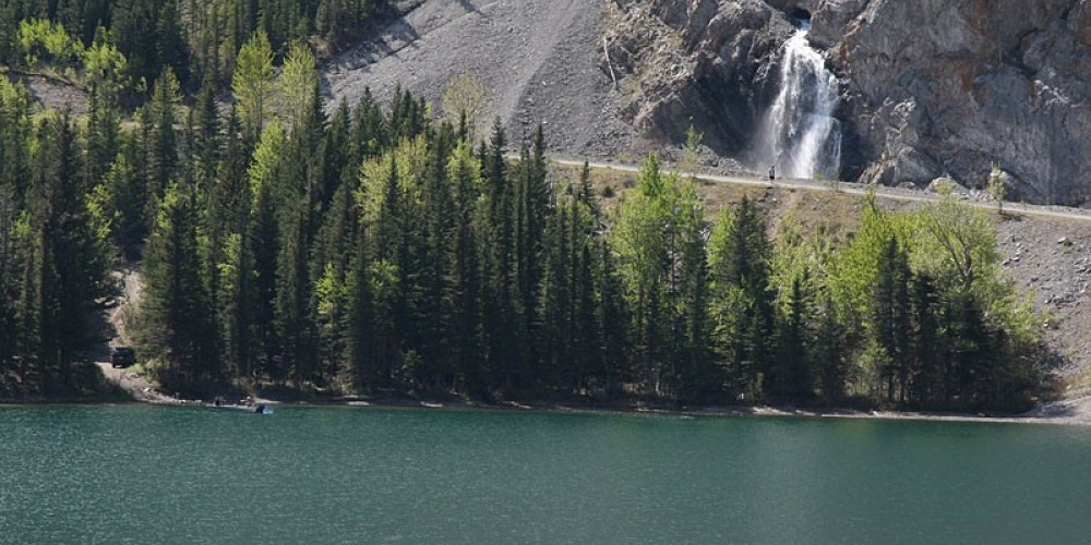 Hikers inspect ephemeral falls while anglers launch craft, lower left. – David Thomas