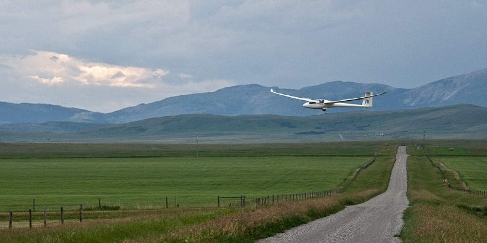 Glider swishes across fields on landing approach to Cowley airstrip. – David Thomas