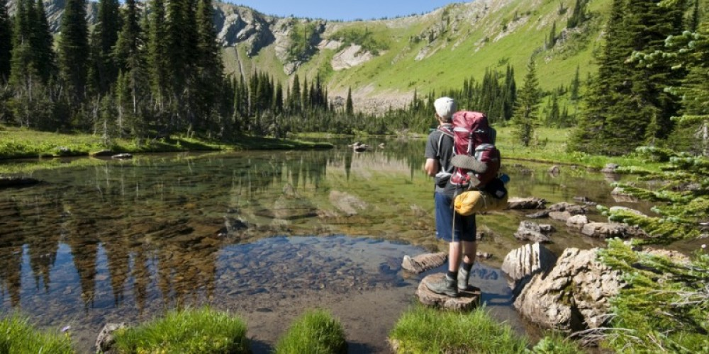 Jewel Reflections, The photographers son enjoying crystal-clear waters of Picnic Lakes in the Jewel Basin. – Ian Cameron