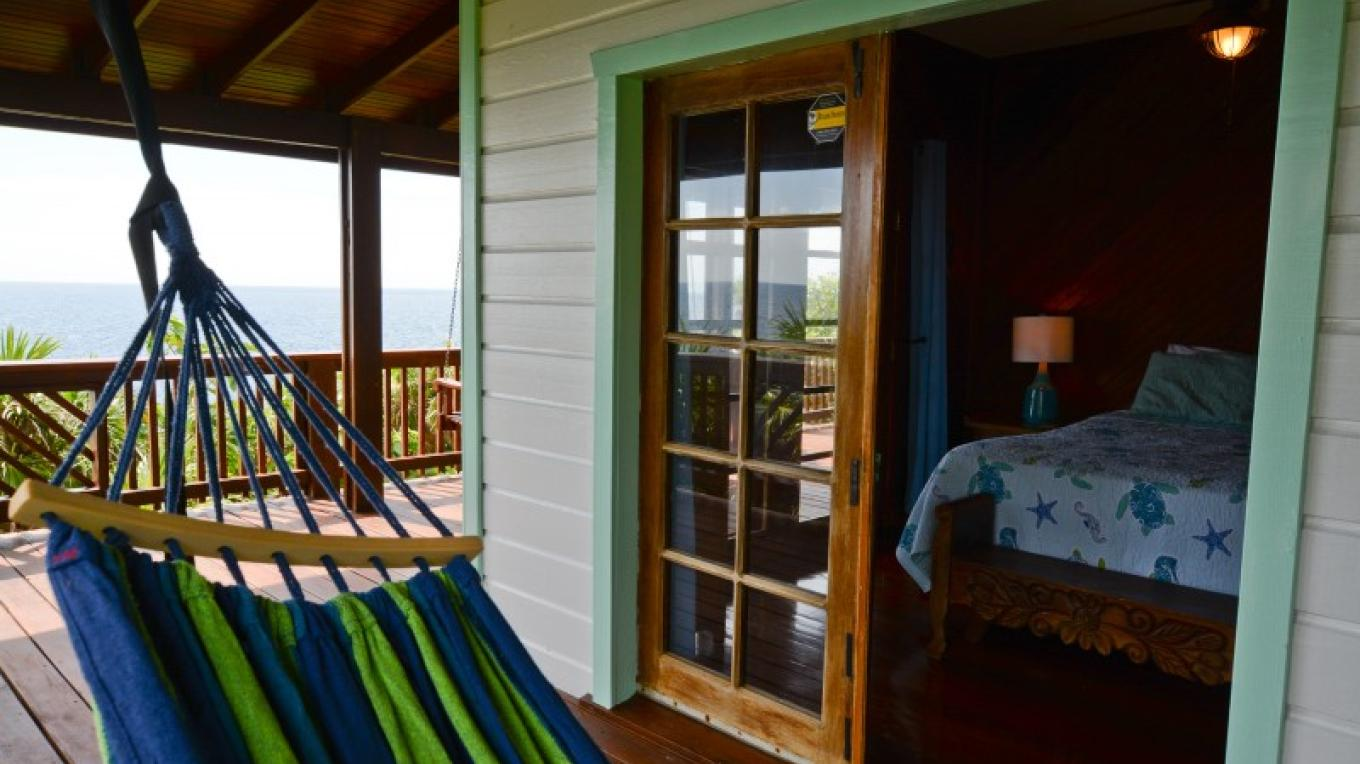 The queen bedroom at Annabel opens onto the 360 wrap around deck with hammocks and porch swing. – Ruth Healey-Elmore