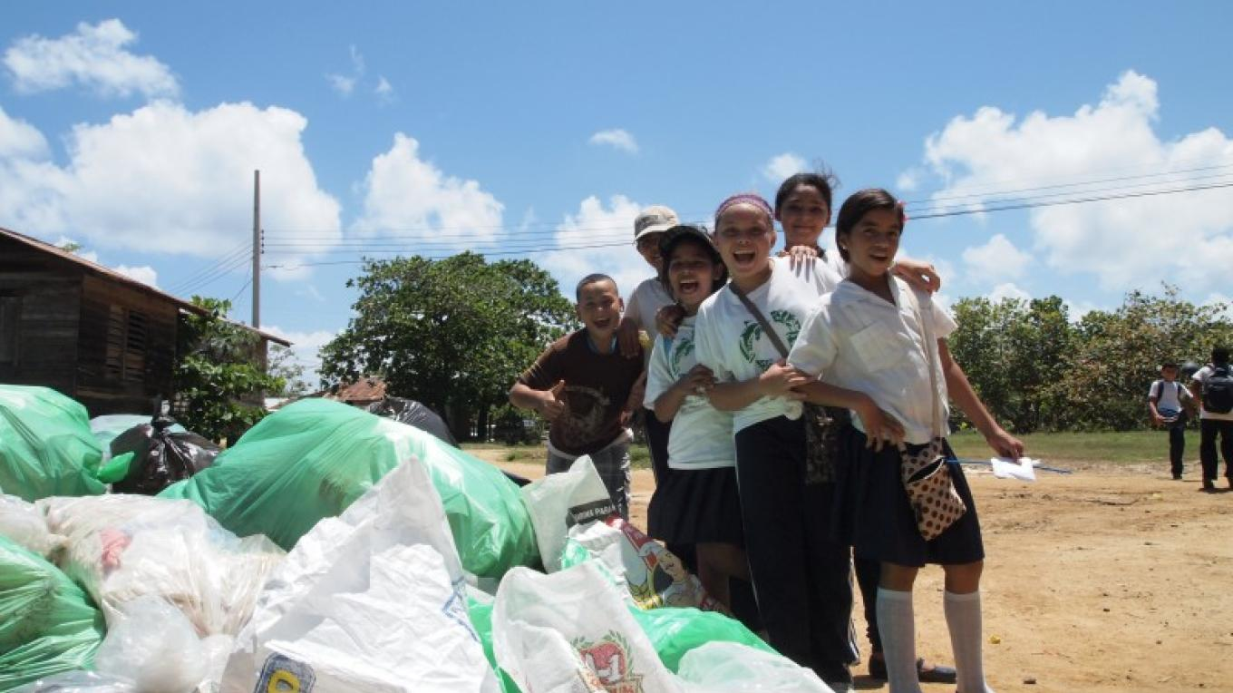 Young elementary students from West End pose next to a large pile of garbage. – Manlio Martinez