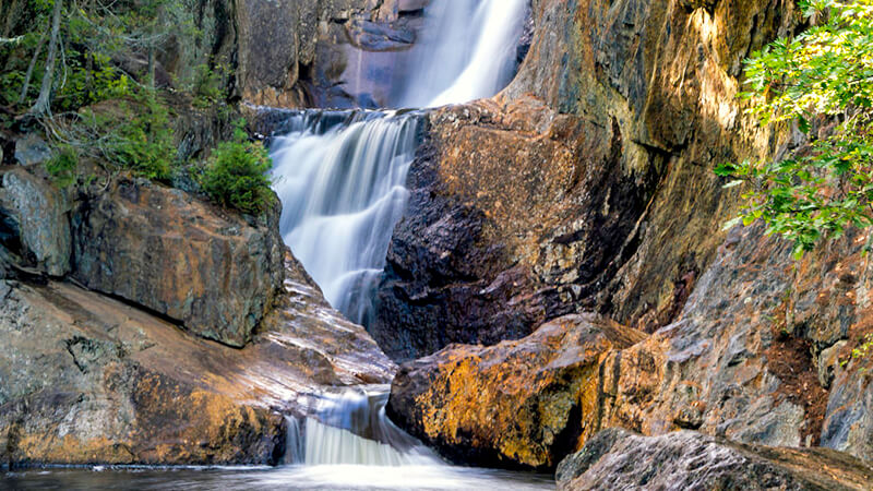 Admire the colorful rocks at Small Falls as you relax in the water.