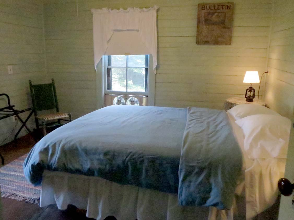 A private room with queen bed, shared bathrooms, shared kitchen, living/dining room, and library.