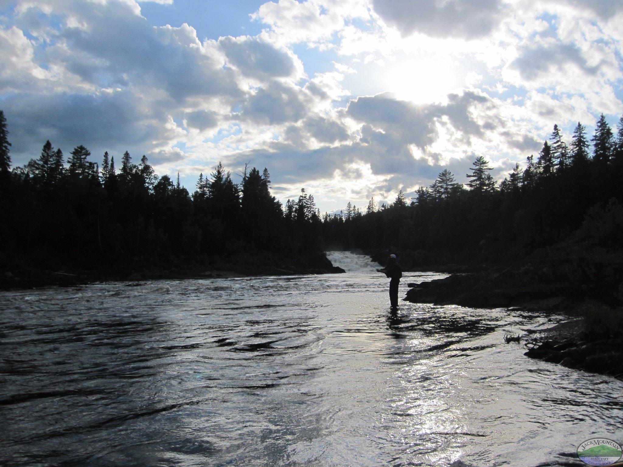 Fishing below Allagash falls on a remote canoe trip under a dramatic Aroostook County sky.