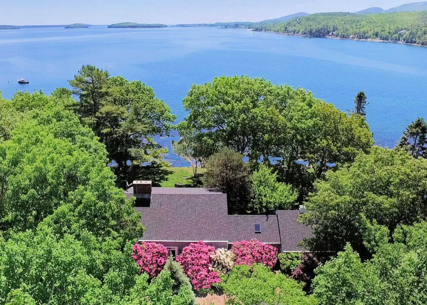 View over the Oceansedge property to Hulls Cove, Bar Harbor Yacht Club and Gilded Age mansions on shoreline, Cadillac Mountain range, the Town's waterfront and boat basin, the Porcupine Islands, the North Atlantic beyond.