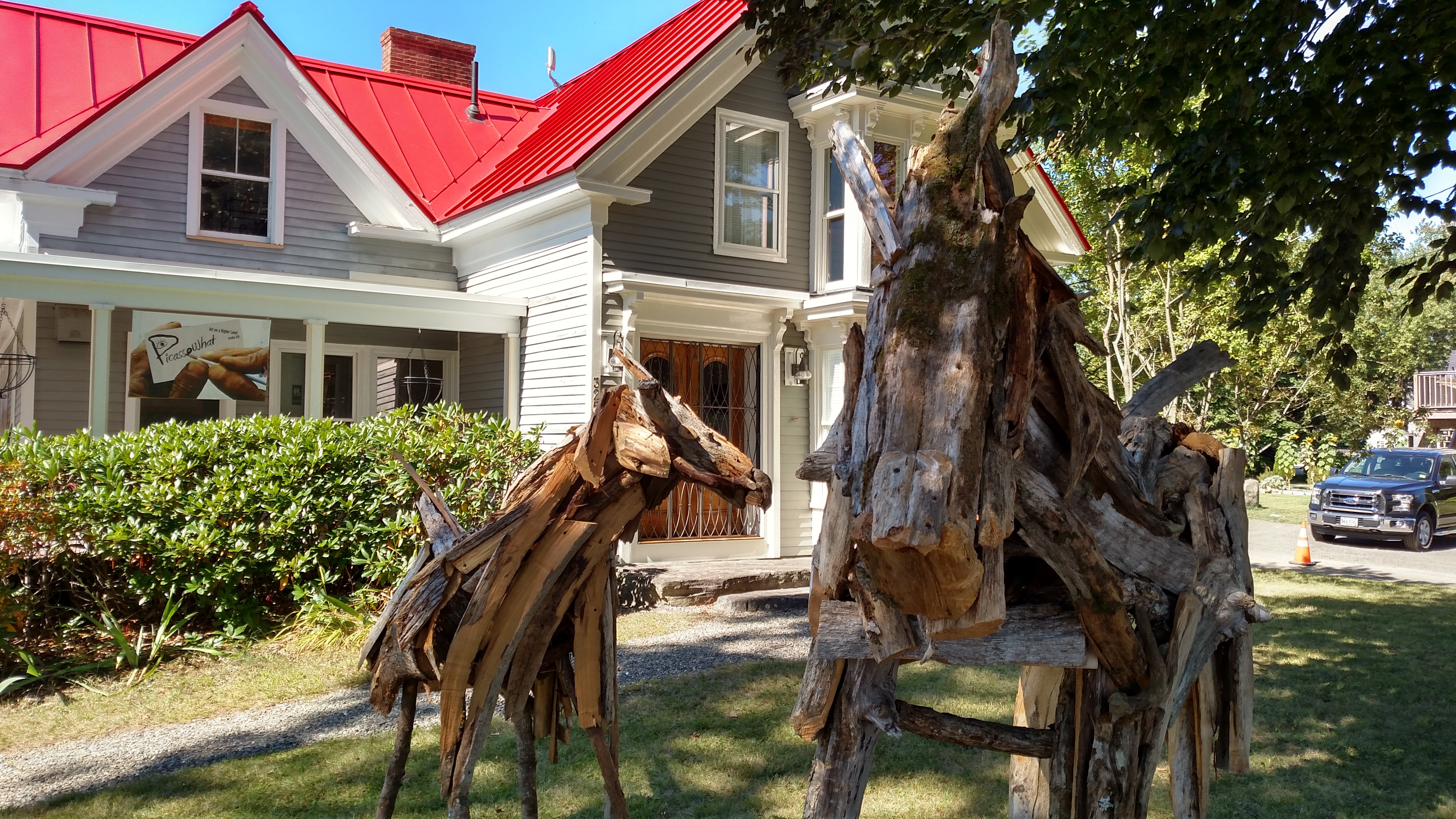 Michael Good Gallery exterior photograph. Historic farmhouse with red roof, and two wood animal sculptures by Maine artist Richard Allen on front lawn.