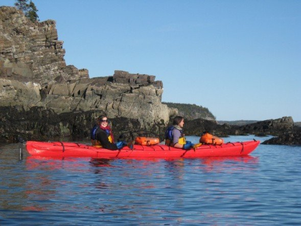 Kayaking past exposed layers of sea cliff rock millions of years old