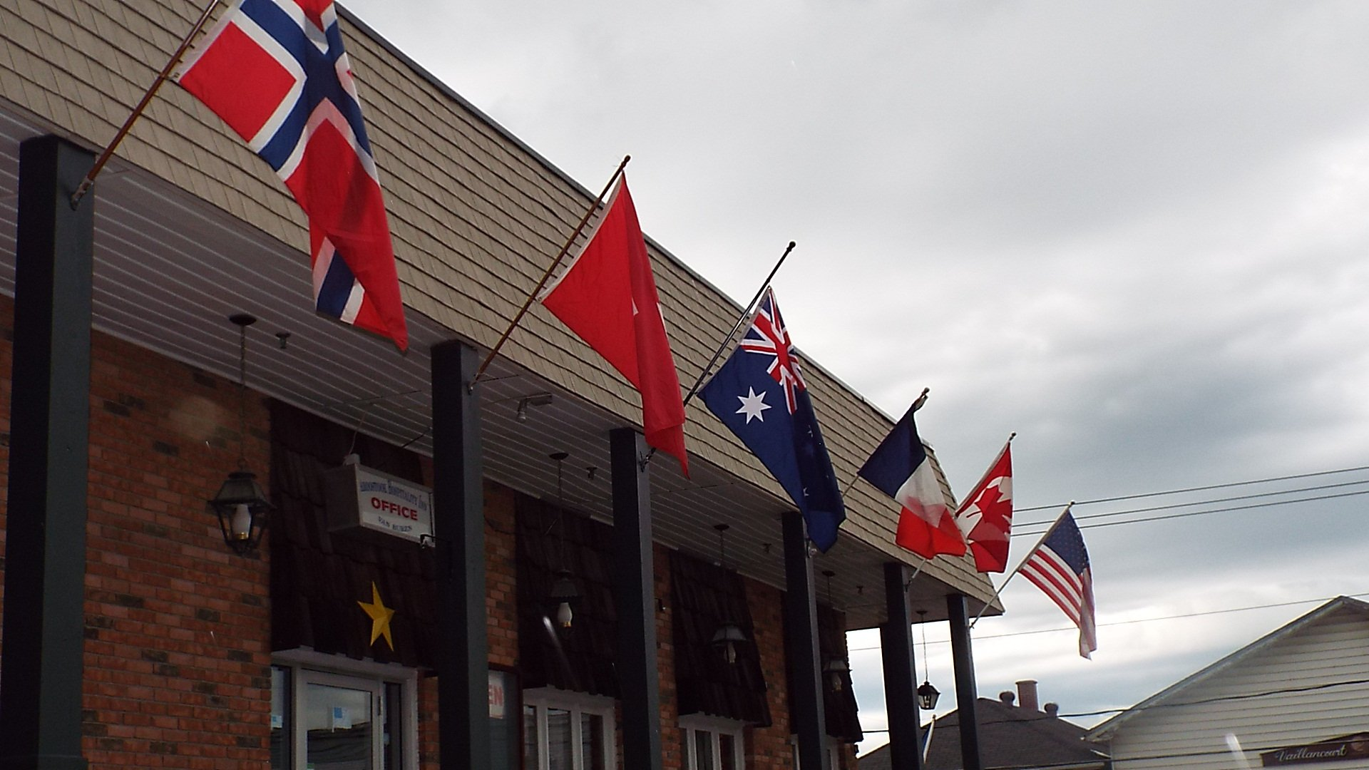 The parking lot side of the Aroostook Hospitality Inn Van Buren. Theses are some of the Countries coming to visit us this summer. Can you identify them?