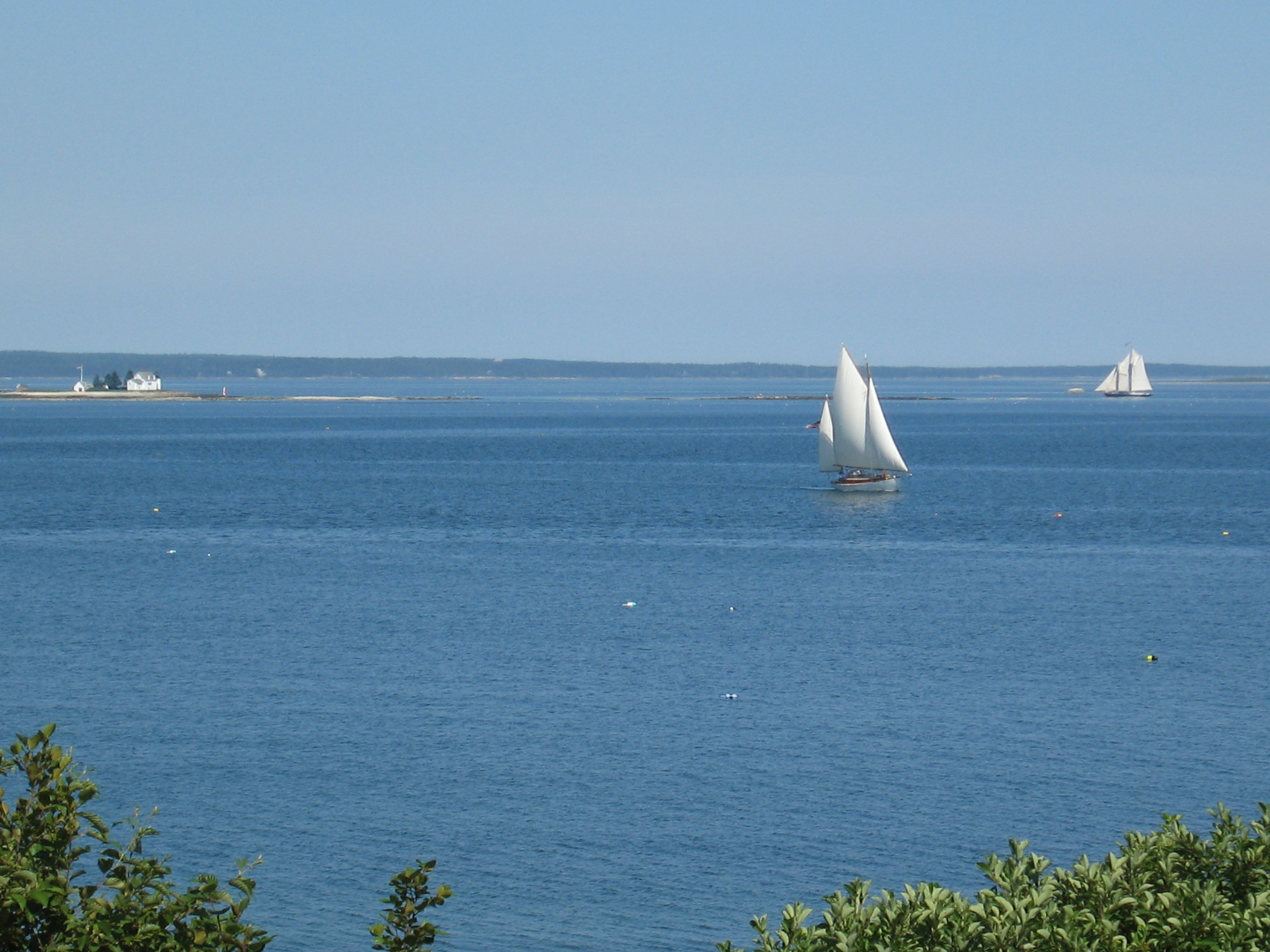sailboat in the bay in front of the cottage