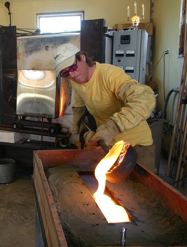 Charlie Jenkins Casts Molten Glass into a sand mold.