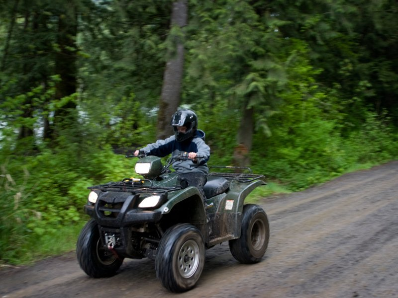 Young boy driving an ATV on a trail in Maine.