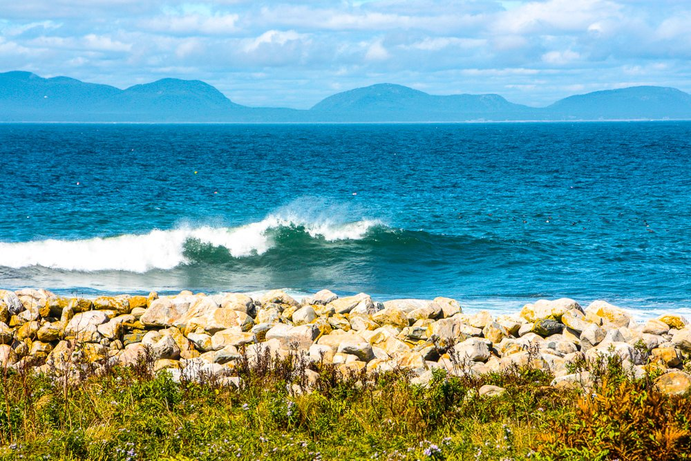 Waves rolling in to the shore. Acadia mountains in the background.
