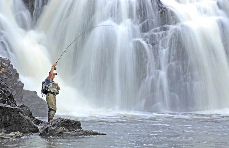 Man fly fishing at Grand Falls on the Dead River.