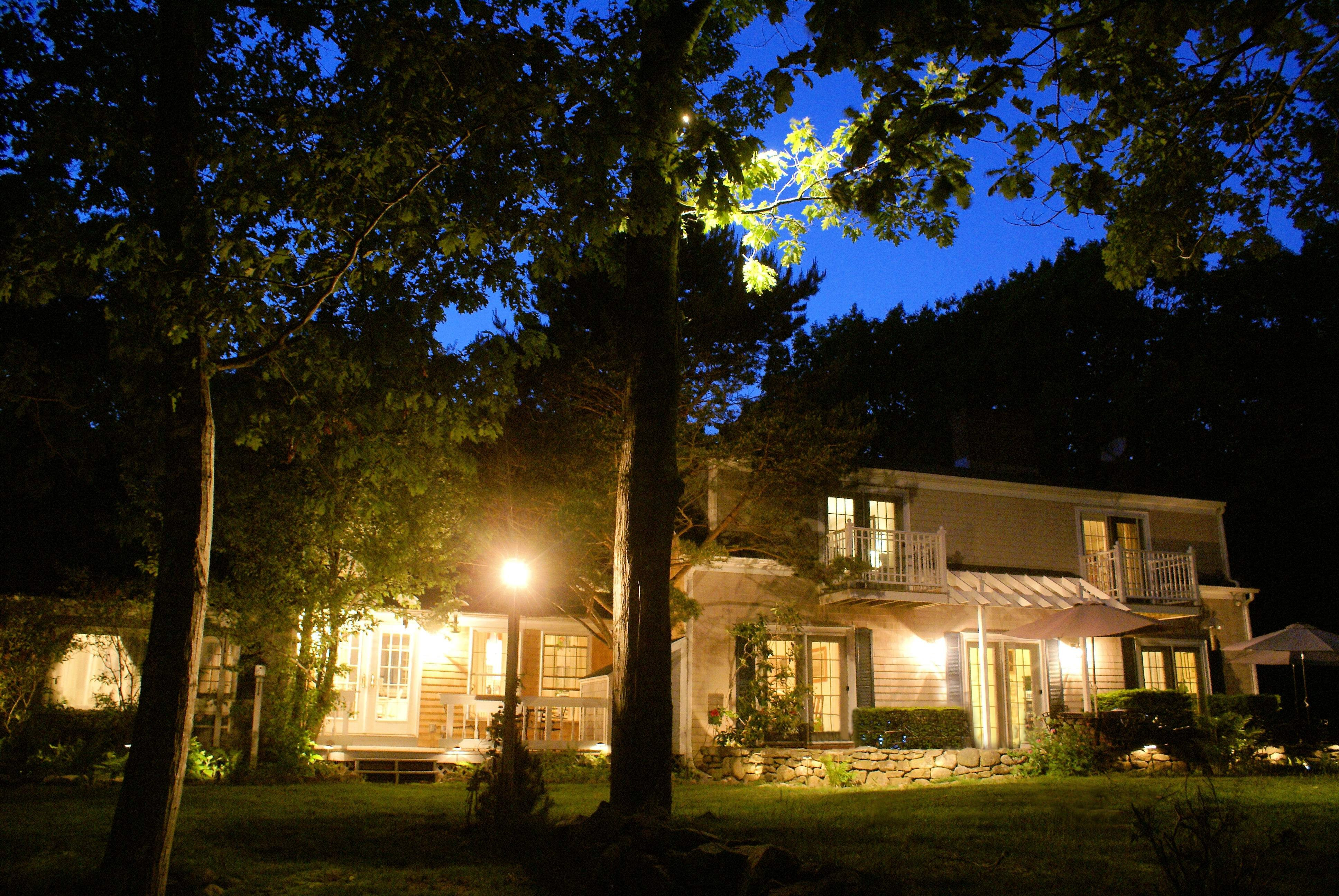 View of the subject property on a summer night. The grounds of the whole property (front and back, up and down a 1000' driveway, and at the driveway entrance) is illuminated by over 100 ground lights.