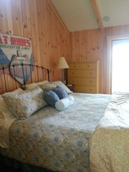 """First Light Cottage - Master bedroom w/king bed, ensuite bath with oversized shower w/dual """"rain"""" shower heads, private small screen porch, water views."""