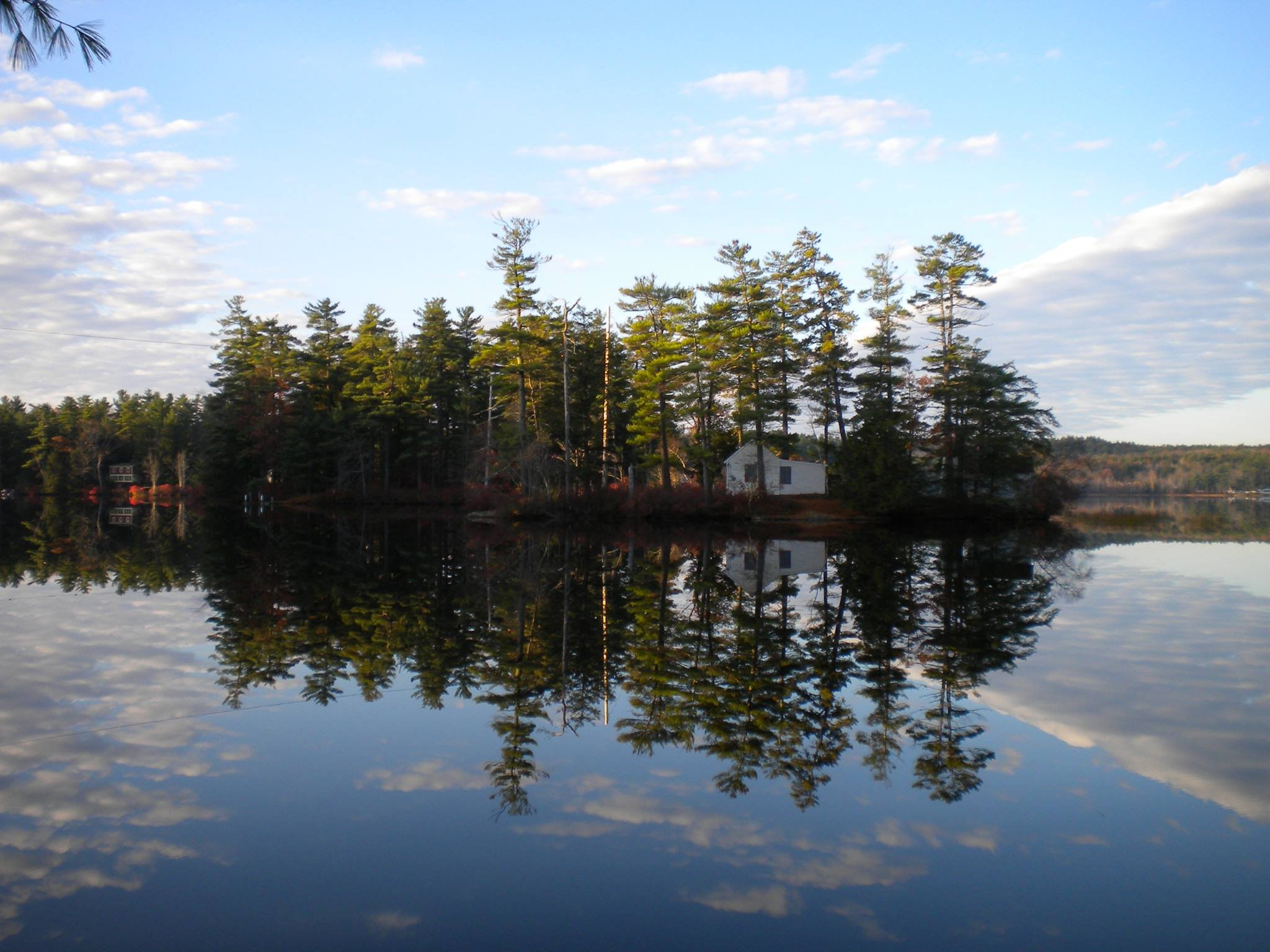 A clear view of tiny Loon Island on a perfectly calm day on Forest Lake, Gray, ME