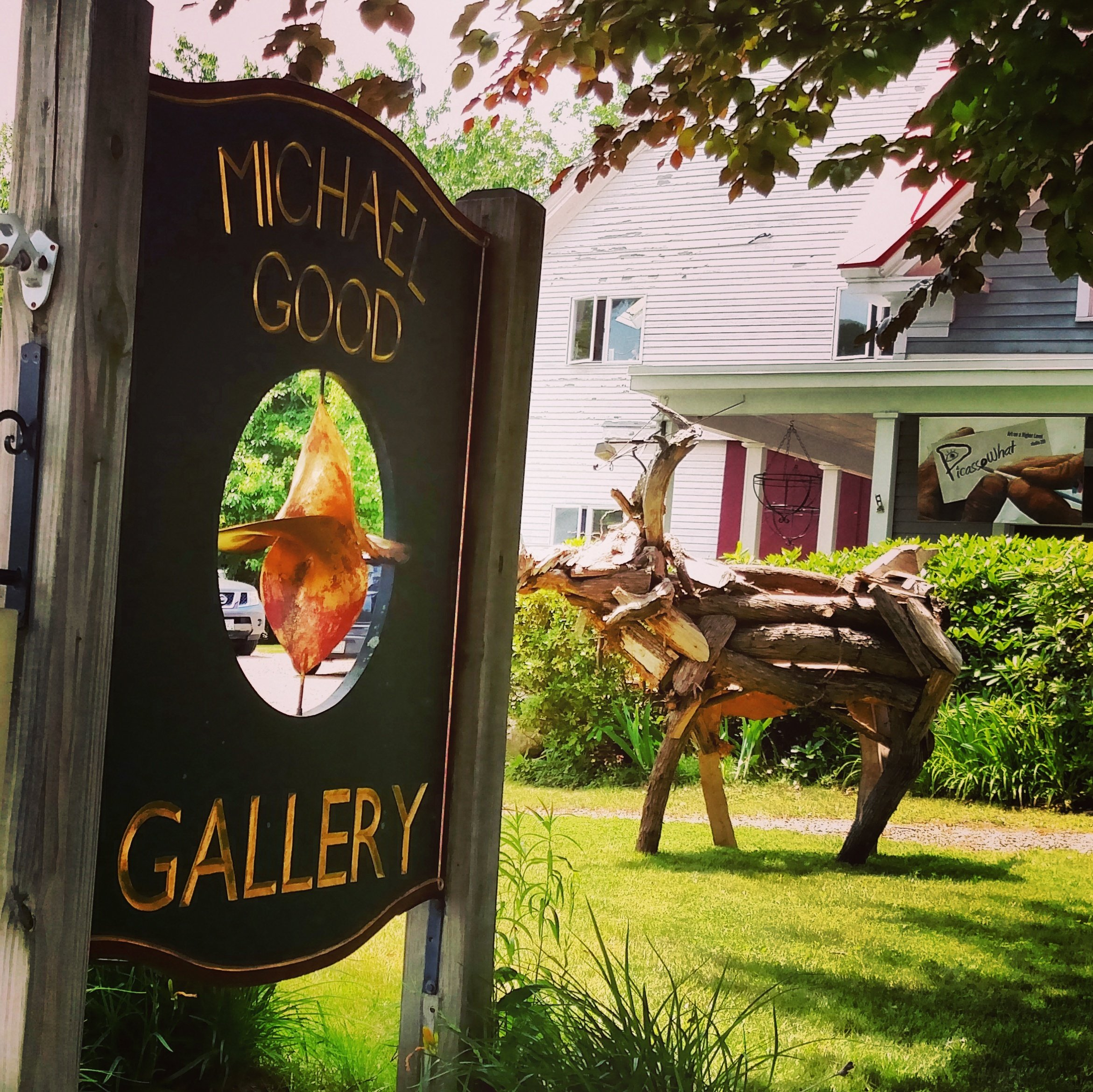 Michael Good Gallery location photograph. Outdoor front lawn sign with Richard Allen's Moose in background.