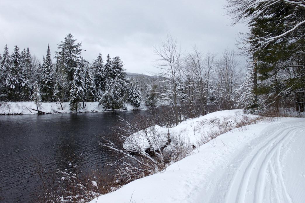 Winter trail runs along river.