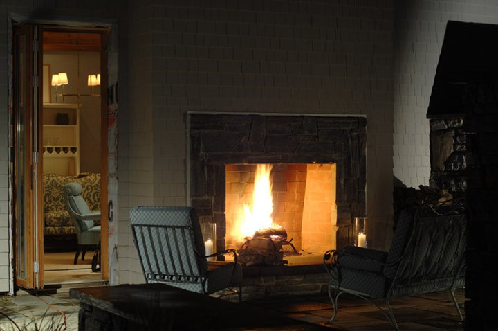 Outdoor Poolhouse fireplace and seating area at The Inn at Ocean's Edge