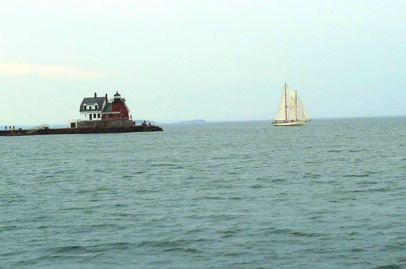 A windjammer sails past the Rockland Breakwater Light